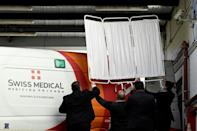 Private security personnel cover the ambulance transporting Diego Maradona