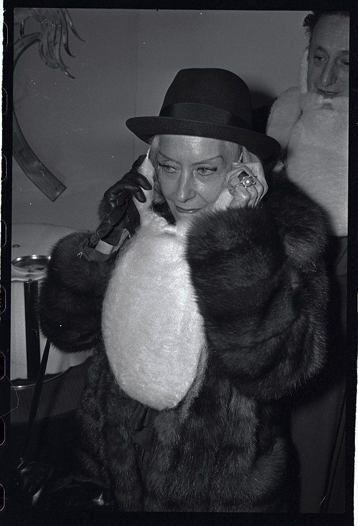 <p>Legendary film star, Gloria Swanson, dresses the part for Christmas with a Santa wig while attending a holiday party. </p>