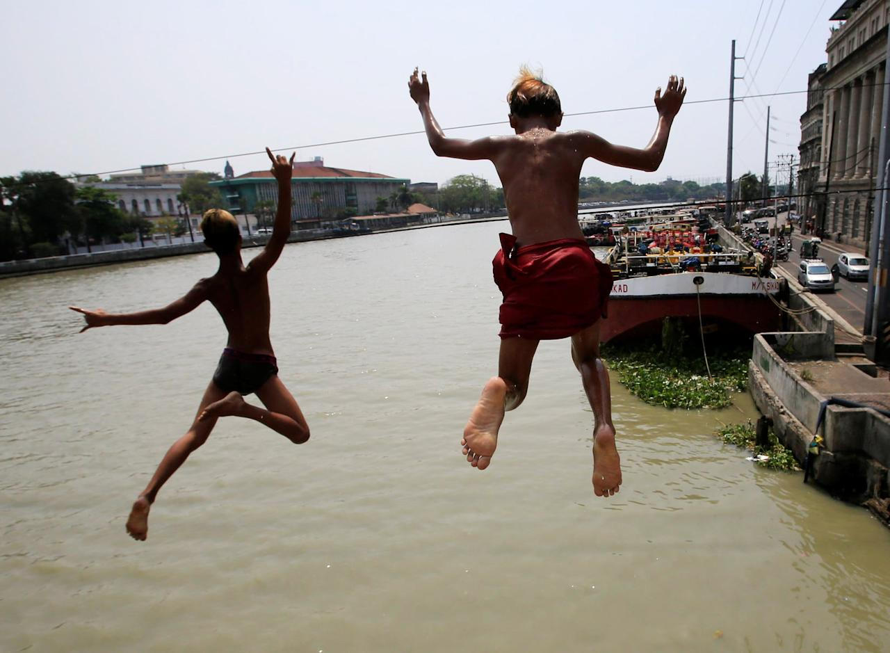 Teenagers dive into the polluted water of Manila Bay ahead of World Water Day in Tondo city, Metro Manila, Philippines March 21, 2018. REUTERS/Romeo Ranoco