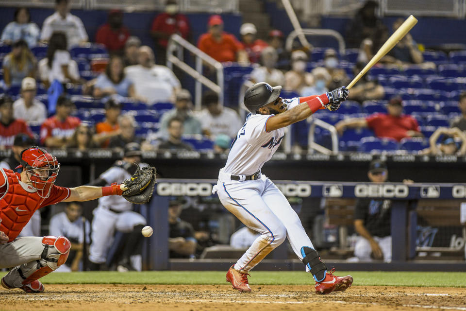 Miami Marlins' Bryan De La Cruz, right, reacts after striking out and getting hit by the ball during the eighth inning of a baseball game against the Miami Marlins, Sunday, Oct. 3, 2021, in Miami. (AP Photo/Gaston De Cardenas)