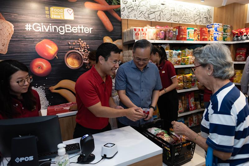 Minister for Social and Family Development Desmond Lee (red shirt) and Mountbatten SMC MP Lim Biow Chuan (blue shirt) at the opening of the Community Shop@Mountbatten. (PHOTO: OCBC)