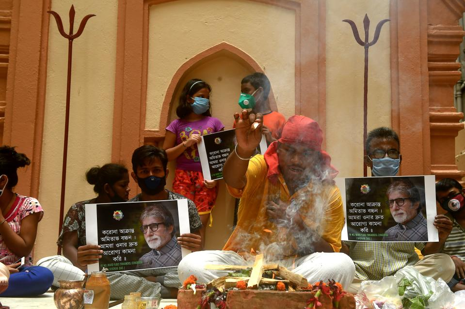 Fans of Bollywood actor Amitabh Bachchan hold posters of the actor while a priest (C) performs special rituals and prayers for his recovery as he tested positive for COVID-19, at a temple in Kolkata on July 12, 2020. - Bollywood megastar Amitabh Bachchan, 77, tested positive for COVID-19 on July 11 and was admitted to hospital in Mumbai, with his actor son Abhishek -- who also announced he had the virus -- saying both cases were mild. (Photo by Dibyangshu SARKAR / AFP)