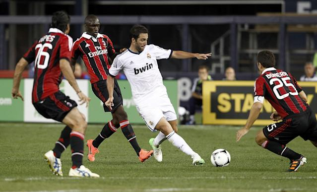 NEW YORK - AUGUST 08: Gonzalo Higuain #20 of Real Madrid drives into Daniele Bonera #25 of A.C. Milan during their match at Yankee Stadium on August 8, 2012 in New York City. (Photo by Jeff Zelevansky/Getty Images)