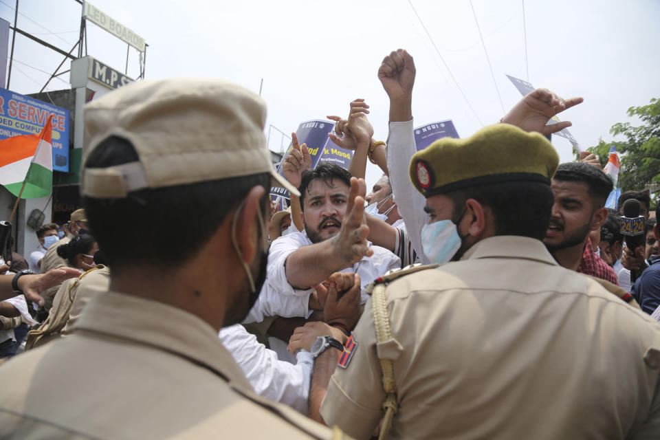 Members of National Students' Union of India scuffle with police during protest marking the second anniversary of Indian government scrapping Kashmir's semi- autonomy in Jammu, India, Thursday, Aug. 5, 2021. On Aug. 5, 2019, Indian government passed legislation in Parliament that stripped Jammu and Kashmir's statehood, scrapped its separate constitution and removed inherited protections on land and jobs. (AP Photo/Channi Anand)