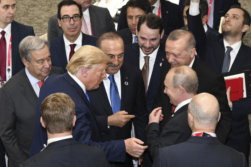 FILE - In this Saturday, June 29, 2019 file photo, U.S President Donald Trump, center left, talks with Russian President Vladimir Putin, center right, as Turkey's President Recep Tayyip Erdogan, second right, and United Nations Secretary-General Antonio Guterres, second left, look on, on the sidelines of the G-20 summit in Osaka, Japan. The Thursday, March 26, 2020 virtual meeting of the Group of 20 nations, with more than a dozen heads of state participating, was less a global summit and more of a high-powered conference call. It lasted about 90 minutes — the same as a standard soccer match — instead of the usual, more languid two days. (Presidential Press Service via AP, Pool)