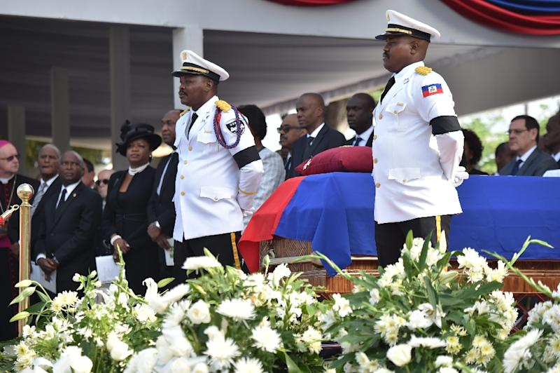 Police officers from the National Palace stand next to the casket of former Haitian president Rene Preval during the State Funeral at the kioske Occide Jeanty, in Port-au-Prince, on March 11, 2017 (AFP Photo/HECTOR RETAMAL)