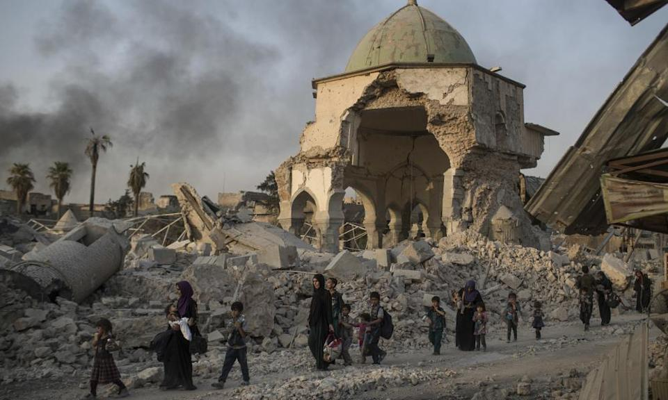 Women and children file past the heavily damaged al-Nuri mosque as they flee Mosul in July 2014.