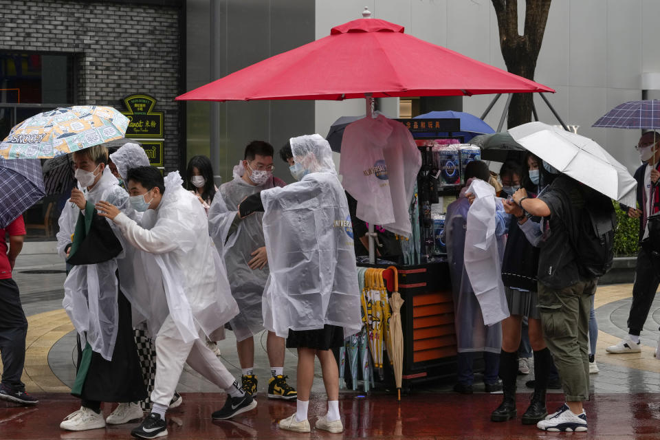 Visitors wearing face masks to help protect themselves from the coronavirus purchase raincoats from a store at the Universal Studios Beijing in Beijing, Monday, Sept. 20, 2021. Thousands of people brave the rain visit to the newest location of the global brand of theme parks which officially opens on Monday. (AP Photo/Andy Wong)