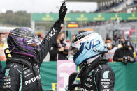 Mercedes driver Lewis Hamilton of Britain, left with teammate Mercedes driver Valtteri Bottas of Finland wave to the crowds after the end of qualifying for Sunday's Formula One Turkish Grand Prix at the Intercity Istanbul Park circuit in Istanbul, Turkey, Saturday, Oct. 9, 2021. Hamilton who took pole position will start 10th due to a penalty with Bottas who came second promoted to pole. (Umit Bektas/Pool Photo via AP)