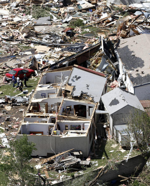 RE-TRANS FOR IMPROVED TONING - People examine the damage in the Oaklawn neighborhood in Wichita, Kan., on Sunday, April 15, 2012, caused by one of several tornadoes that hit the state on Saturday. (AP Photo/Jeff Tuttle)