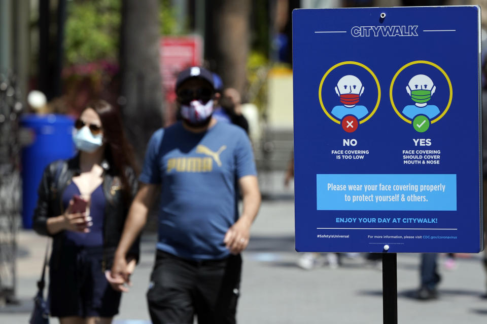 FILE - In this May 14, 2021, file photo, signs instruct visitors on the proper way to wear masks at the Universal City Walk in Universal City, Calif. California is keeping its rules for wearing facemasks in place until the state more broadly lifts its pandemic restrictions on June 15. State officials said Monday, May 17 that the delay will give people time to prepare, and for the state to make sure that virus cases stay low. (AP Photo/Marcio Jose Sanchez, File)