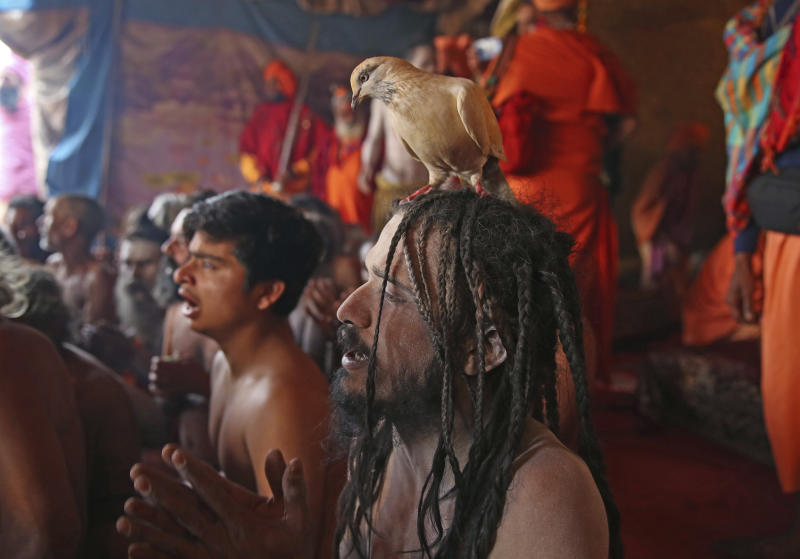In this Jan. 27, 2019, photo, Hindu holy men of monastic order Juna Akhara participate in a ritual before becoming Naga Sadhus or naked holy men at Sangam, the confluence of three holy rivers during the Kumbh Mela or pitcher festival in Prayagraj Uttar Pradesh state, India. At every Kumbh, including this year's, thousands of devotees were initiated into the reclusive sect of the Naga Sadhus, naked, ash-smeared cannabis-smoking Hindu warriors and onetime-armed defenders of the faith who for centuries have lived as ascetics in jungles and caves. (AP Photo/Rajesh Kumar Singh)