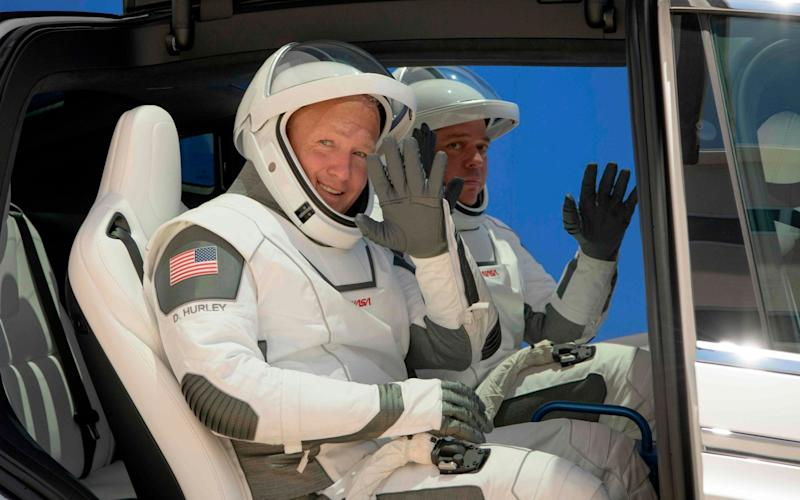NASA astronauts Douglas Hurley, left, and Robert Behnken, wearing SpaceX spacesuits, are seen as they depart the Neil A. Armstrong Operations and Checkout Building for Launch Complex 39A - NASA/NASA
