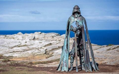 The carving at the opening of Merlin's Cave, an 8ft bronze sculpture named after the Cornish word for power - Credit: Getty Images