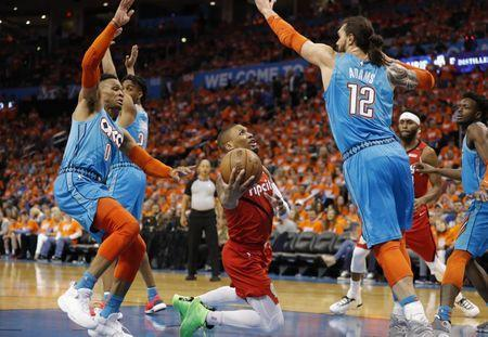 Apr 19, 2019; Oklahoma City, OK, USA; Portland Trail Blazers guard Damian Lillard (middle) shoots against Oklahoma City Thunder guard Russell Westbrook (left) and center Steven Adams (right) during the second half in game three of the first round of the 2019 NBA Playoffs at Chesapeake Energy Arena. Mandatory Credit: Alonzo Adams-USA TODAY Sports