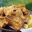 """<p>Catfish were readily abundant in the Antebellum South and, due to their status as """"bottom feeders,"""" weren't deemed the most stylish dinner staples. Once the South's seafood secret, mild-flavored catfish has gained popularity nationwide. Simply soak the catfish in milk for an hour <a href=""""https://www.myrecipes.com/fried-recipes"""" rel=""""nofollow noopener"""" target=""""_blank"""" data-ylk=""""slk:before frying"""" class=""""link rapid-noclick-resp"""">before frying</a> to eliminate any leftover fishy taste. The cornmeal crust creates a perfect light and crispy texture. The catfish are done when """"most of the bubbling stops and the fillets begin to float.""""</p>"""