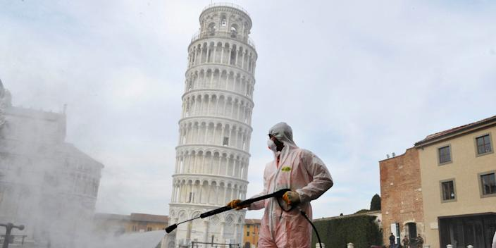 A worker sanitizes the Piazza dei Miracoli near to the Tower of Pisa in Pisa, Italy, on March 17 2020.