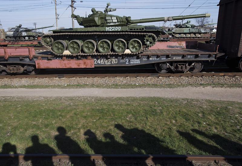 Russian officers look as Russian tanks T-72B, close center, arrive and Ukrainian tanks, back, are transported to the Ukraine at the Ostryakovo railway station not far from Simferopol, Crimea, Monday, March 31, 2014. Russian tanks T-72B will be stationed on former Ukrainian military bases. (AP Photo/Pavel Golovkin)