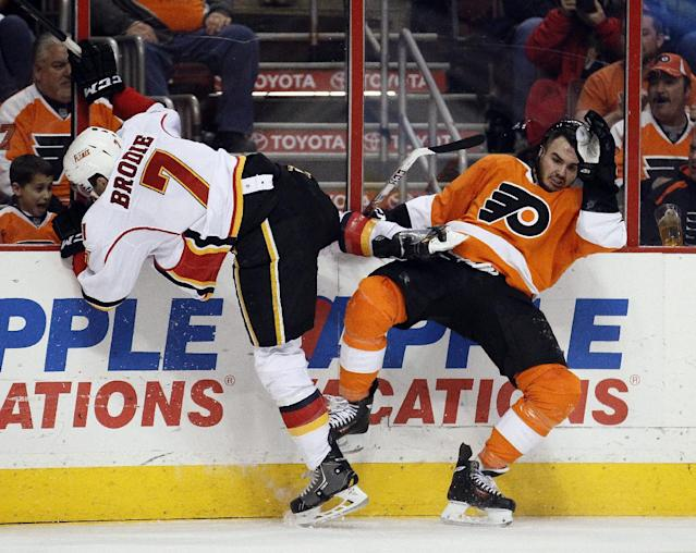Calgary Flames' TJ Brodie, left, and Philadelphia Flyers' Zac Rinaldo fall after colliding along the boards during the second period of an NHL hockey game, Saturday, Feb. 8, 2014, in Philadelphia. (AP Photo/Tom Mihalek)