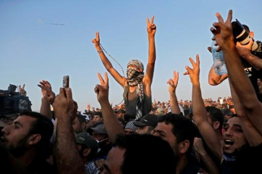 Supporters of Hamas leader Ismail Haniya react during his speech near the border with Israel east of Gaza City on May 15, 2018