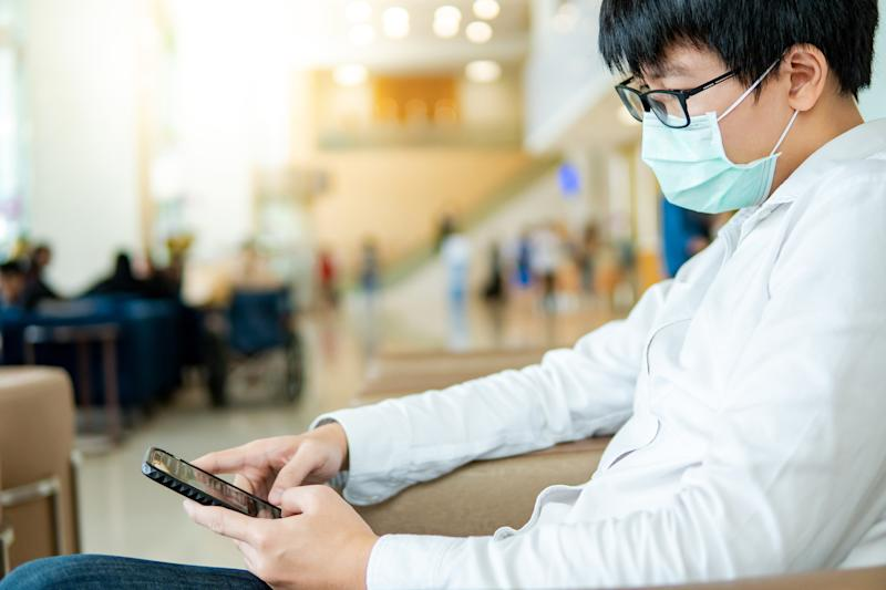 Male Asian patient wearing surgical mask using smartphone at waiting area in hospital or medical center. Medical exam or body check up. Wuhan coronavirus outbreak prevention. Health care concept