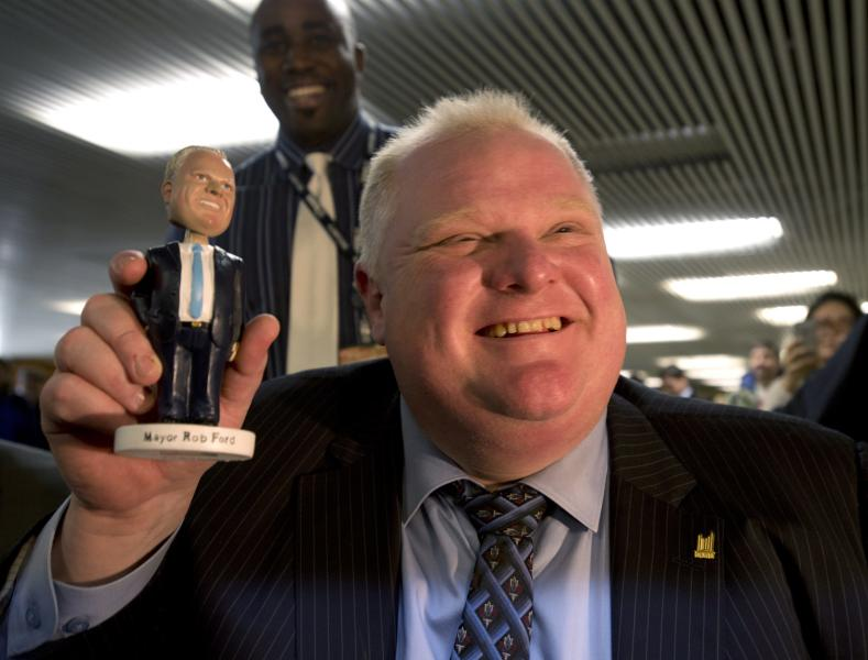 "Toronto Mayor Rob Ford holds a Rob Ford bobblehead doll at Toronto city hall on Tuesday, Nov. 12, 2013. Up to 300 people lined up at City Hall Tuesday to buy the ""Robbie Bobbie"" dolls for $20 each, with the proceeds going to charity. The mayor has been dogged by accusations of drug and alcohol abuse. (AP Photo/The Canadian Press, Frank Gunn)"