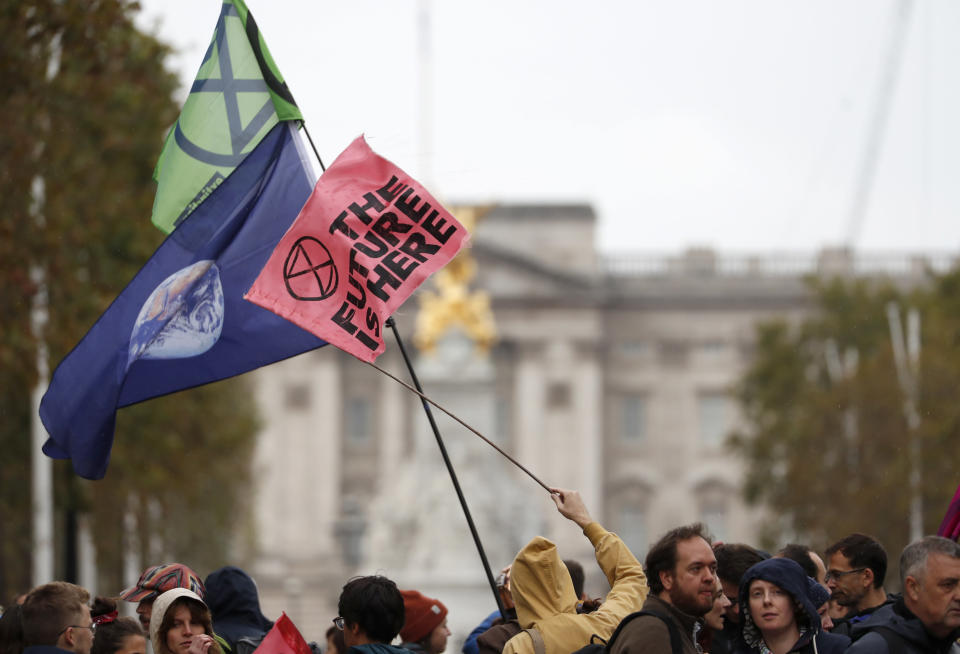 Climate protestors block the Mall leading to Buckingham Palace, rear, central London Monday, Oct. 7, 2019. Activists with the Extinction Rebellion movement blocked major roads in London, Berlin and Amsterdam on Monday at the beginning of what was billed as a wide-ranging series of protests demanding new climate policies. (AP Photo/Alastair Grant)
