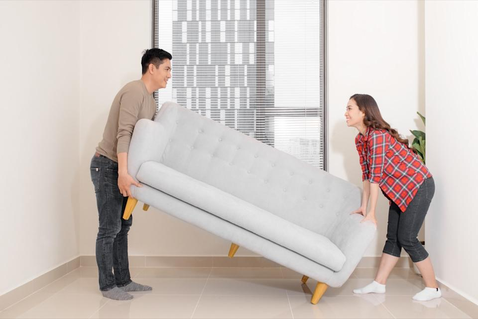 Couple rearranging furniture in their living room moving a couch together