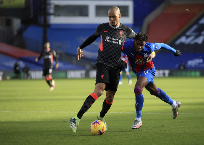 Liverpool's Fabinho, left, duels for the ball with Crystal Palace's Wilfried Zaha during the English Premier League soccer match between Crystal Palace and Liverpool at Selhurst Park stadium in London, Saturday, Dec. 19, 2020. (Adam Davy/Pool via AP)