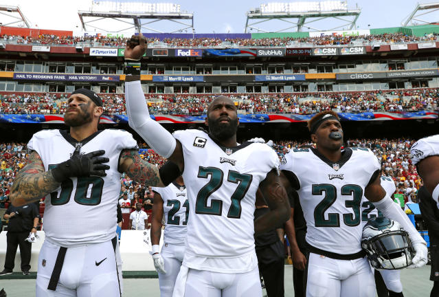 <p>Philadelphia Eagles strong safety Malcolm Jenkins, center, raises his fist as he stands between teammates Chris Long, left, and Rodney McLeod during a rendition of the national anthem before an NFL football game against the Washington Redskins, Sunday, Sept. 10, 2017, in Landover, Md. (AP Photo/Alex Brandon) </p>