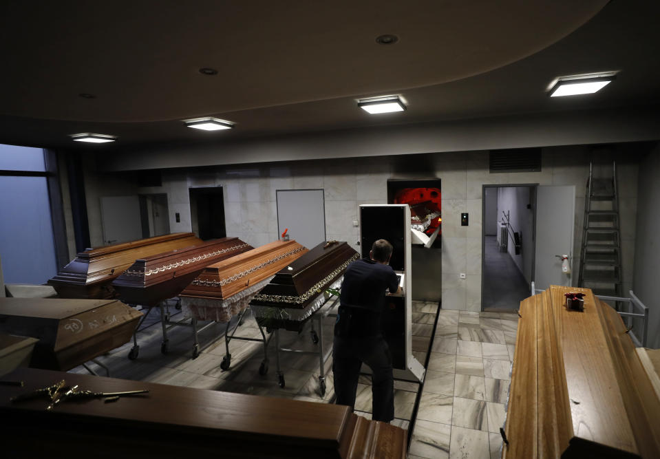 """FILE - In this Thursday, Jan. 7, 2021 file photo, a worker moves a casket to be incinerated at a crematorium in Ostrava, Czech Republic. After the European Union passed the death toll of half a million citizens lost to the coronavirus on Wednesday, Feb. 10, 2021, the EU Commission chief said that stalling rollout of the vaccines could be partly blamed on the bloc being over-optimistic, over-confident and plainly """"too late."""" (AP Photo/Petr David Josek, File)"""