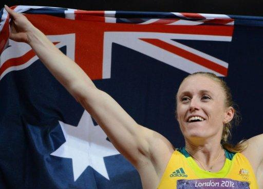Australia's Sally Pearson celebrates with her national flag after winning the women's 100m hurdles final