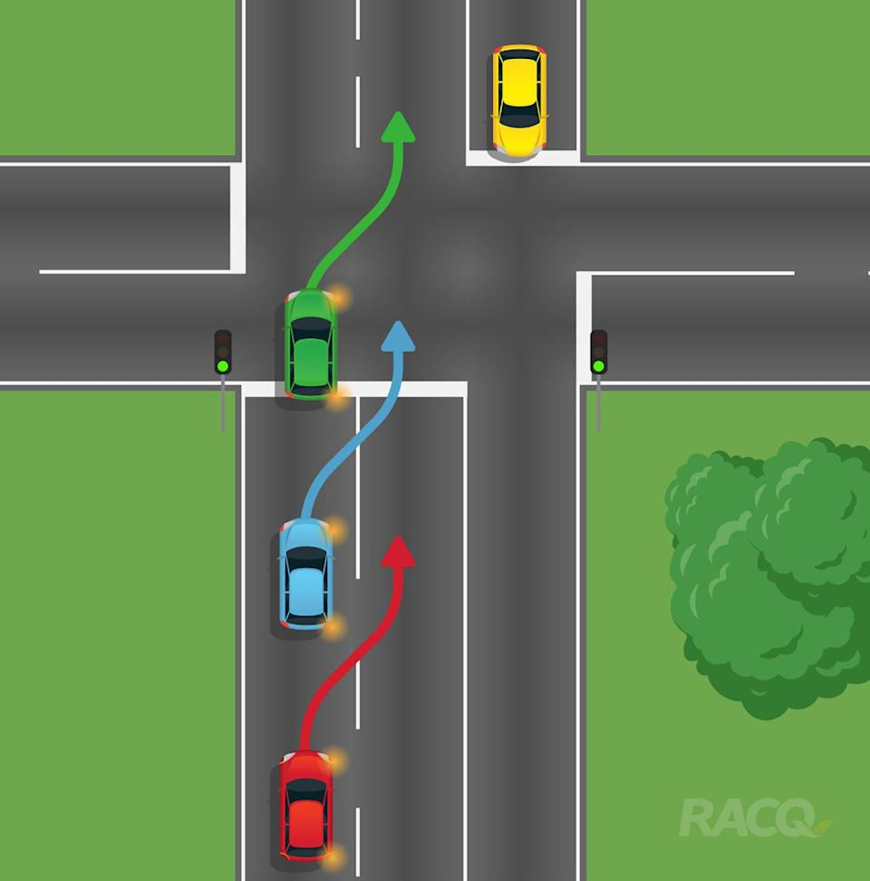 Three cars are pictured preparing to change lanes at an intersection.