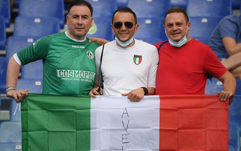 Italy fans pose with a flag inside the stadium before the match - Reuters