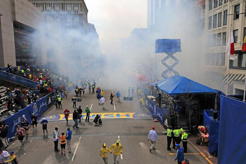 Medical workers aid injured people at the 2013 Boston Marathon following an explosion in Boston, Monday, April 15, 2013. Two explosions shattered the euphoria of the Boston Marathon finish line on Monday, sending authorities out on the course to carry off the injured while the stragglers were rerouted away from the smoking site of the blasts. (AP Photo/The Boston Globe, David L Ryan)  MANDATORY CREDIT