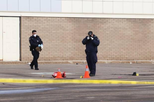 Officers photograph items, including a pair of shoes, in a parking lot near Dooly's on Elmwood Drive in Moncton where a man was killed in a hit and run on Friday.  (Shane Magee/CBC - image credit)