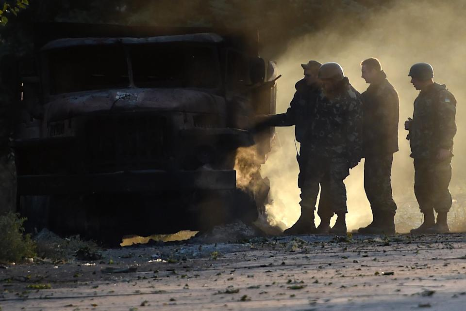 Ukrainian army soldiers check a burnt truck on September 7, 2014 after an overnight bombing attack (AFP Photo/Philippe Desmazes )