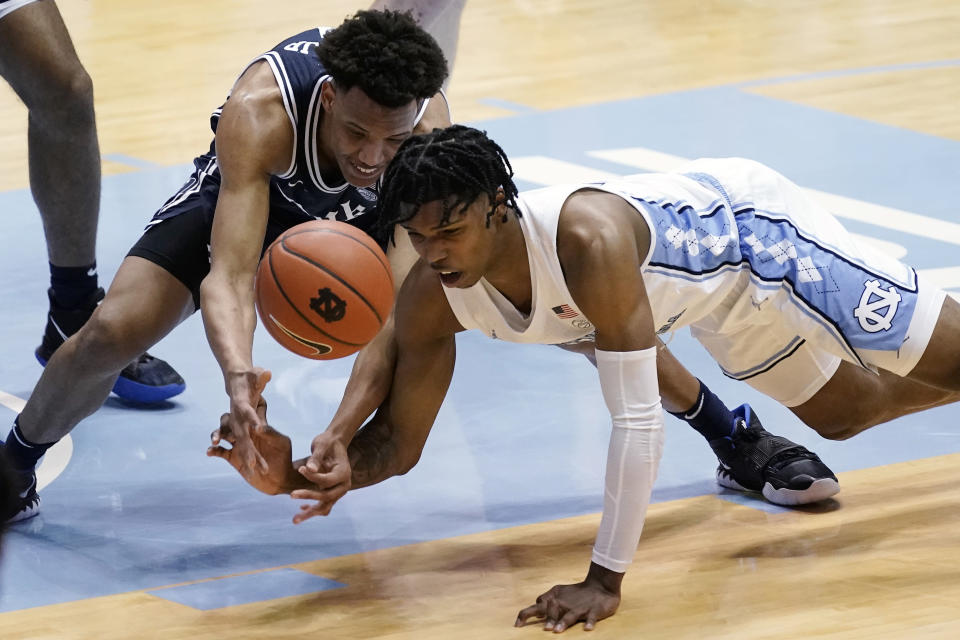Duke forward Wendell Moore Jr. and North Carolina guard Caleb Love, right, struggle for a loose ball during the first half of an NCAA college basketball game in Chapel Hill, N.C., Saturday, March 6, 2021. (AP Photo/Gerry Broome)
