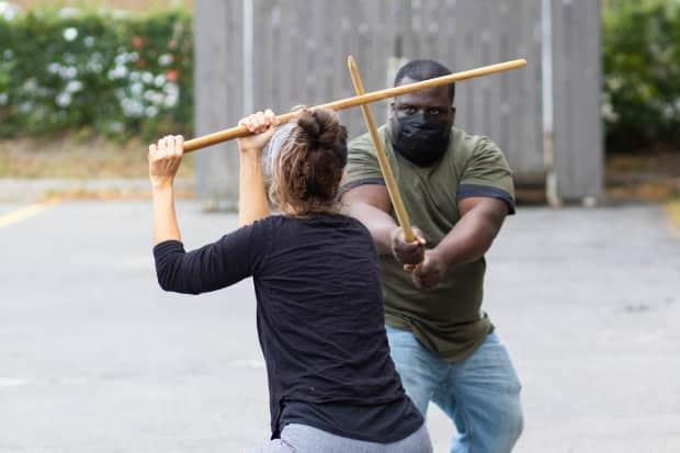 Jennifer Hood and Adrian Jemmott wear masks while practising the Japanese martial art of kenjutsu in a parking lot off Wellington Street West on Aug. 27, 2021. (Trevor Pritchard/CBC - image credit)