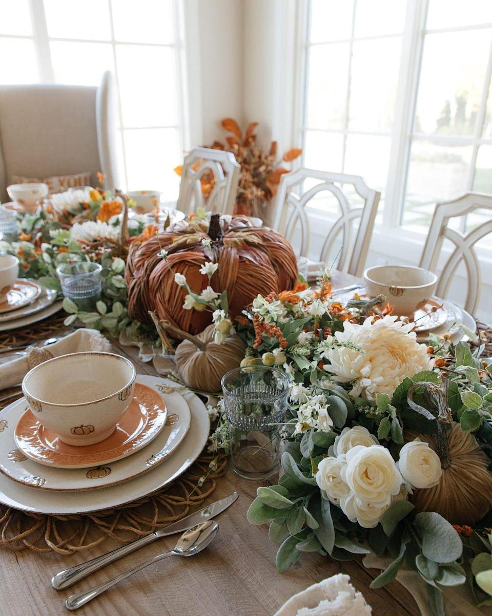 """<p>Not feeling the spooky spirit this year? With festive dishes, fall florals, and a wood pumpkin front and center, this whole table setup screams Halloween elegance. </p><p><strong>Get the tutorial at <a href=""""https://homewithhollyj.com/pumpkin-themed-fall-tablescape/"""" rel=""""nofollow noopener"""" target=""""_blank"""" data-ylk=""""slk:Home With Holly J"""" class=""""link rapid-noclick-resp"""">Home With Holly J</a>. </strong> </p>"""