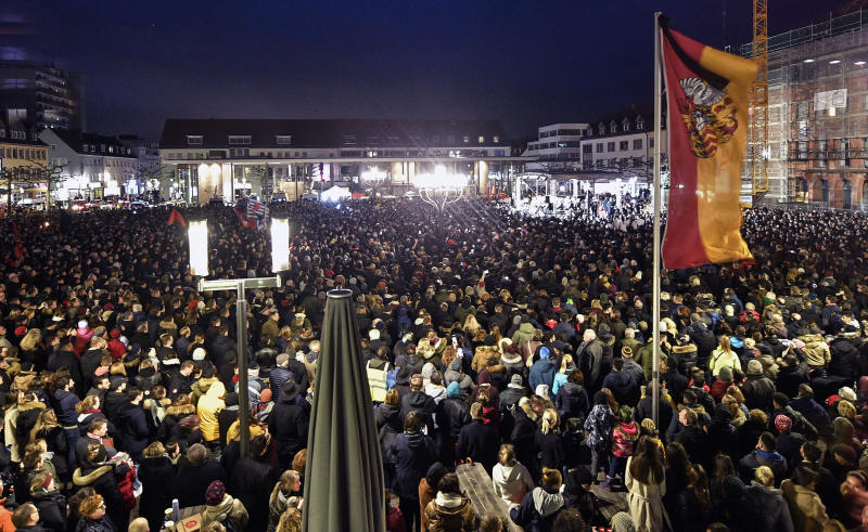 Thousands listen to German president Frank-Walter Steinmeier during a mourning on the market place for the victims of the shooting in Hanau, Germany, Thursday, Feb. 20, 2020. A 43-year-old German man shot and killed nine people at several locations in a Frankfurt suburb overnight in attacks that appear to have been motivated by far-right beliefs, officials said Thursday. (AP Photo/Martin Meissner)