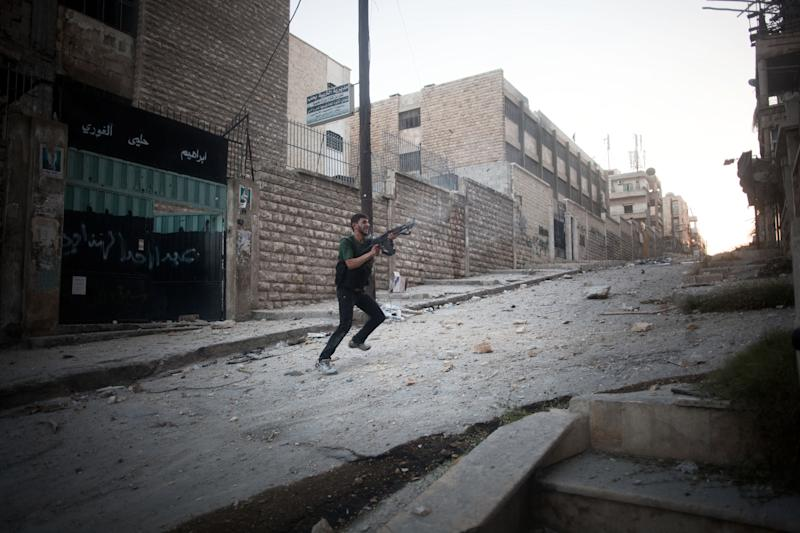 An FSA soldier fires his weapon towards Syrian Army positions in the Izaa district in Aleppo, Syria, Saturday, Sept 8, 2012. On Friday, U.S. Senators John McCain, Joe Lieberman and Lindsay Graham, who have toured the volatile Middle East in recent days, urged Washington to help arm Syria's rebels with weapons and create a safe zone inside the country for a transition government. (AP Photo/ Manu Brabo)