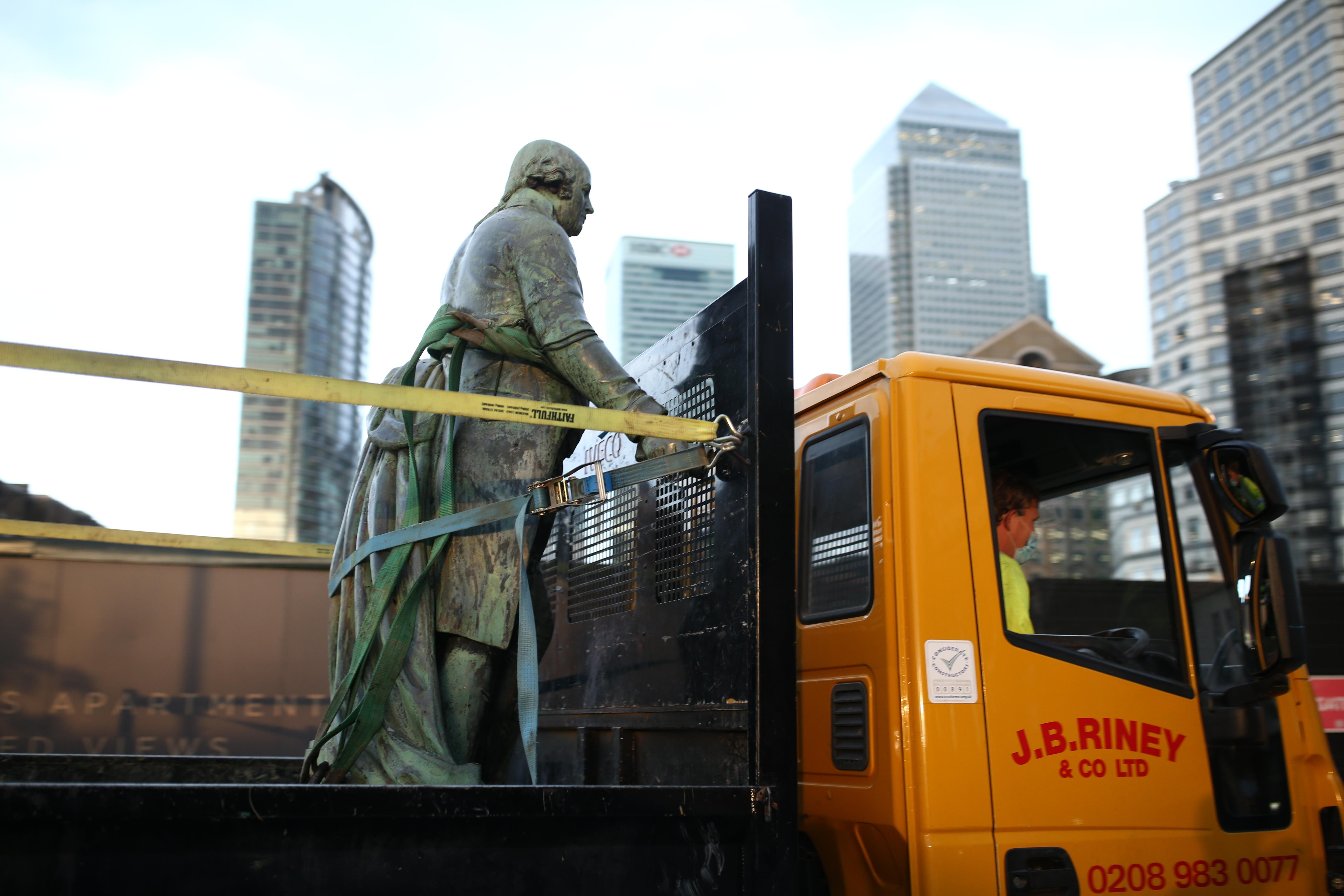 Workers take down a statue of slave owner Robert Milligan at West India Quay, east London as Labour councils across England and Wales will begin reviewing monuments and statues in their towns and cities, after a protest saw anti-racism campaigners tear down a statue of a slave trader in Bristol. (Photo by Yui Mok/PA Images via Getty Images)