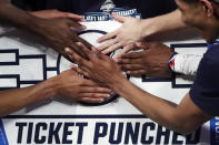 FILE - In this March 16, 2019, file photo, Villanova players stick a logo of their team on a bracket board after defeating Seton Hall 74-72 in an NCAA college basketball game in the championship of the Big East Conference tournament in New York. 30 college conferences are still planning to hold basketball tournaments where the winner earns the automatic bid to the NCAAs. But the leagues also have until Feb. 26, 2021, to notify the selection committee if there will be any changes to how the automatic bid is awarded. (AP Photo/Julio Cortez, File)