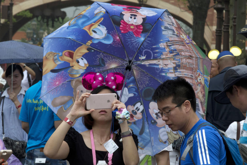 A woman takes photo on her phone during the opening day of the Disney Resort in Shanghai, China, Thursday, June 16, 2016. Walt Disney Co. opened its first theme park in mainland China on Thursday at a ceremony that mixed speeches by Communist Party officials, a Chinese children's choir and actors dressed as Sleeping Beauty and other Disney characters. (AP Photo/Ng Han Guan)