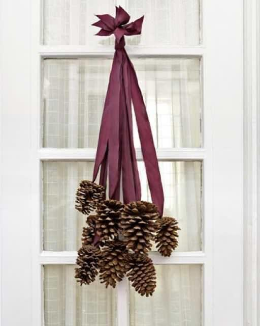 """<p>Browse your backyard for pinecones and use your foraged finds to make this warm and inviting piece for your <a href=""""https://www.countryliving.com/diy-crafts/g2734/christmas-door-decorations/"""" rel=""""nofollow noopener"""" target=""""_blank"""" data-ylk=""""slk:front door"""" class=""""link rapid-noclick-resp"""">front door</a>. </p><p><strong>Step 1: </strong>Cut eight two-foot-long pieces of ribbon.</p><p><strong>Step 1: </strong>Use a hot glue gun to adhere the last two inches of each ribbon to the base of eight four- to six-inch pinecones.</p><p><strong>Step 2: </strong>After the glue dries, collect all the ribbon ends and stagger them so that the cones fall at varying lengths. Tie the ribbon ends together in a knot, trim the tips so they are uniform, and slip the knot over a finishing nail.</p><p><a class=""""link rapid-noclick-resp"""" href=""""https://www.amazon.com/Berwick-McGinley-No-210-Acetate-Burgundy/dp/B0762SSJKP/?tag=syn-yahoo-20&ascsubtag=%5Bartid%7C10050.g.23489557%5Bsrc%7Cyahoo-us"""" rel=""""nofollow noopener"""" target=""""_blank"""" data-ylk=""""slk:SHOP RIBBON"""">SHOP RIBBON</a></p>"""