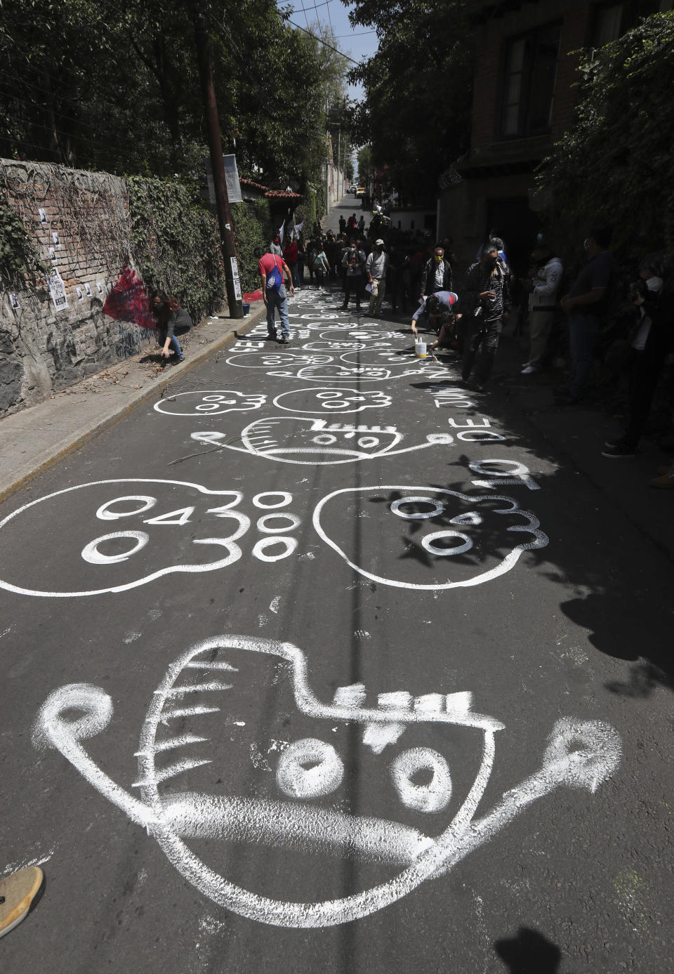 """Protesters paint skulls on the asphalt road outside the residence of former Mexican President Luis Echeverría, (1970-1976), during a march to commemorate the 50th anniversary of the student massacre of 1971 known as """"El Halconazo,"""" in Mexico City, Thursday, June 10, 2021. The attack, also known as the Corpus Christi massacre, was carried out by a group of men apparently recruited by the government to dissolve a pro-democracy student demonstration. (AP Photo/Marco Ugarte)"""