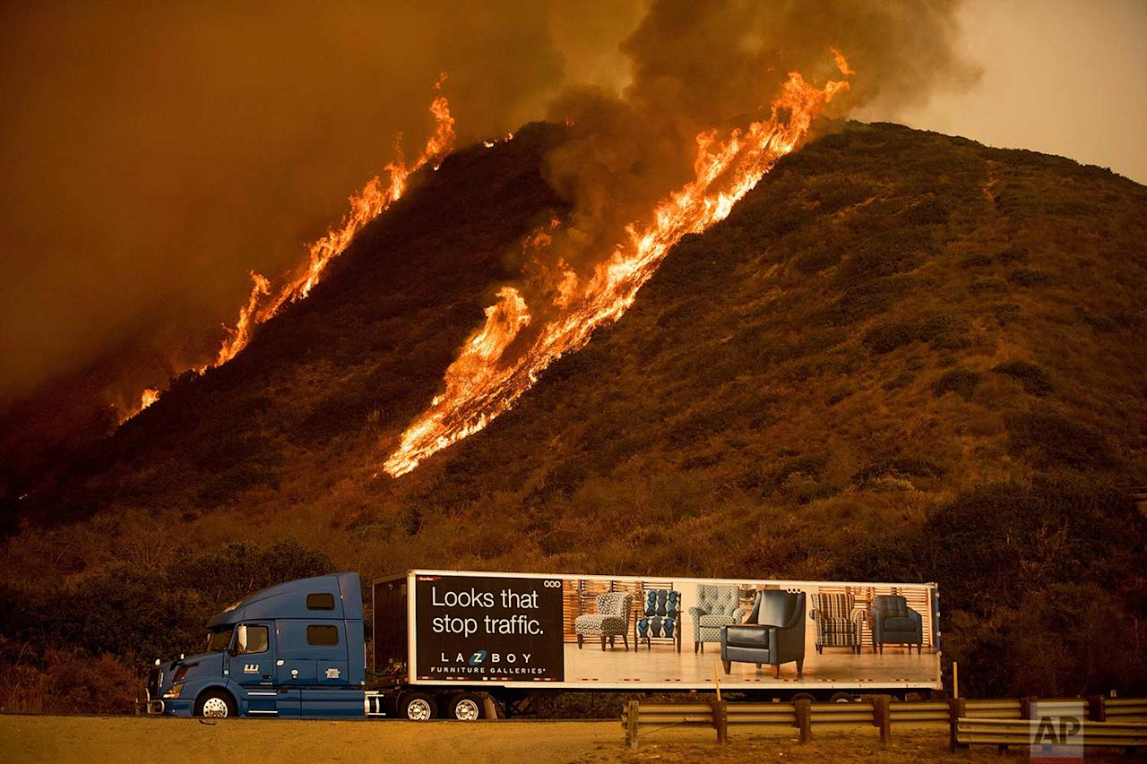 <p>Flames from the Thomas fire burn on a hillside behind a truck on Highway 101 north of Ventura, California. (AP Photo/Noah Berger) </p>