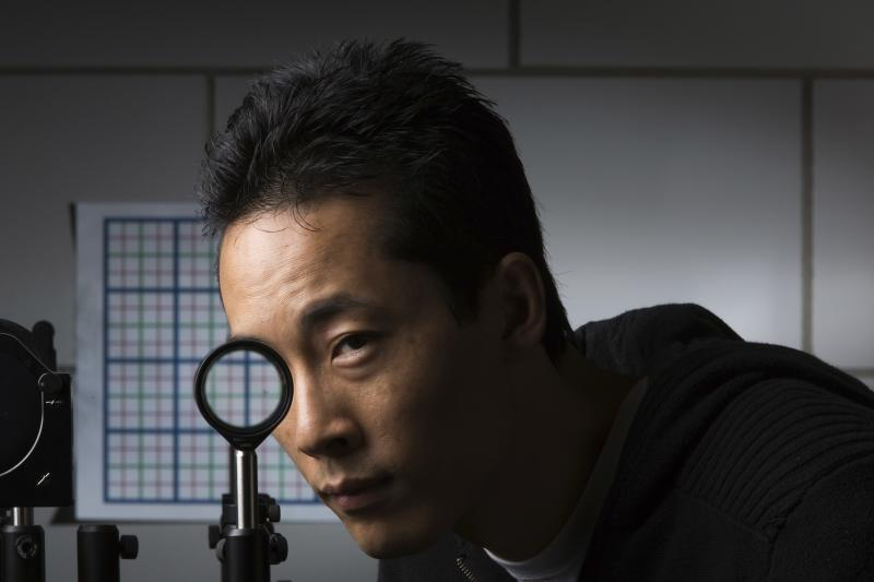 University of Rochester Ph.D. student Joseph Choi demonstrates a cloaking device using four lenses in Rochester, New York in this September 11, 2014 University of Rochester handout photo. Scientists at the University of Rochester have discovered a way to hide large objects from sight using inexpensive and readily available lenses, a technology that seems to have sprung from the pages of J.K. Rowling's Harry Potter fantasy series. Picture taken September 11, 2014.  REUTERS/J. Adam Fenster/University of Rochester/Handout via Reuters  (UNITED STATES - Tags: SCIENCE TECHNOLOGY EDUCATION SOCIETY TPX IMAGES OF THE DAY)