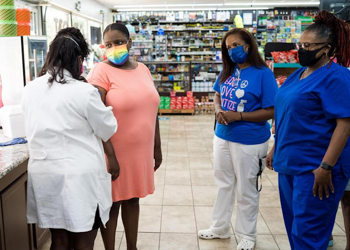 Andrea Whitted-Ellison watches as Dr. Karen Smith prepares to administer her CCovid-19 vaccination at the JL Grocery connvenience store in Raeford, N.C. (Justin Kase Conder / for NBC News)
